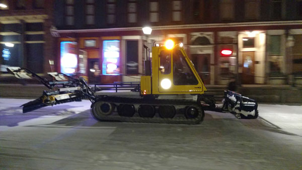 A snowcat smooths out main street for skijoring outside Quincy's steakhouse in Leadville.